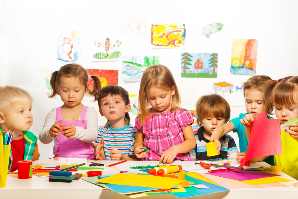 group of young children in a classroom creating colorful art