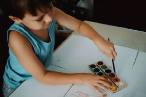 little boy watercoloring on paper