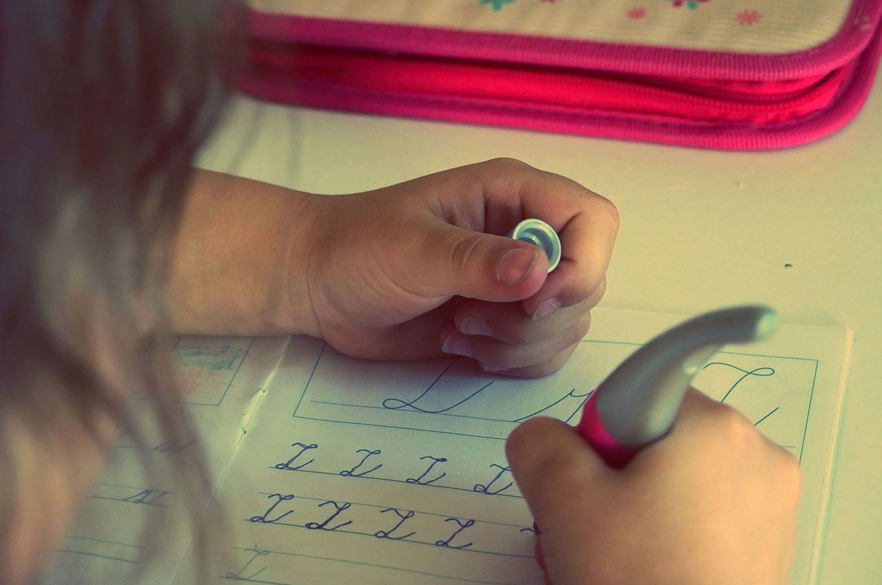 closeup of child learning and practicing cursive handwriting
