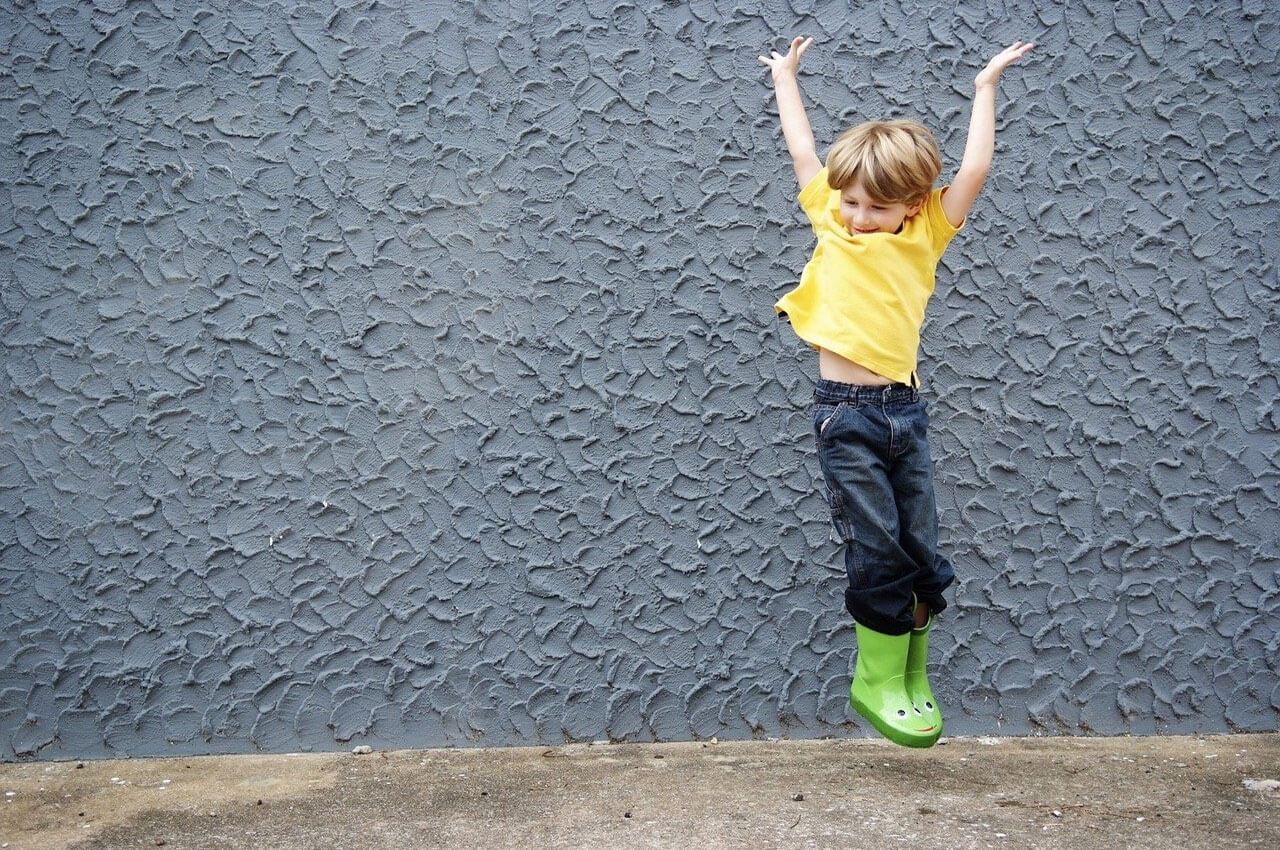 little boy in boots jumping with hands up