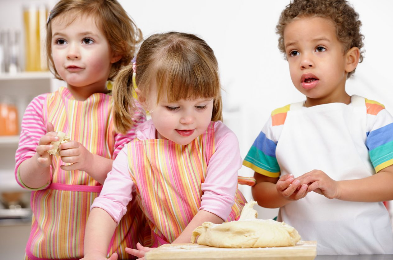 three small children in apron rolling dough