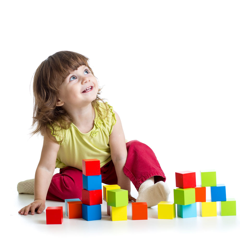 toddler girl looking up smiling surrounded with colorful cube blocks