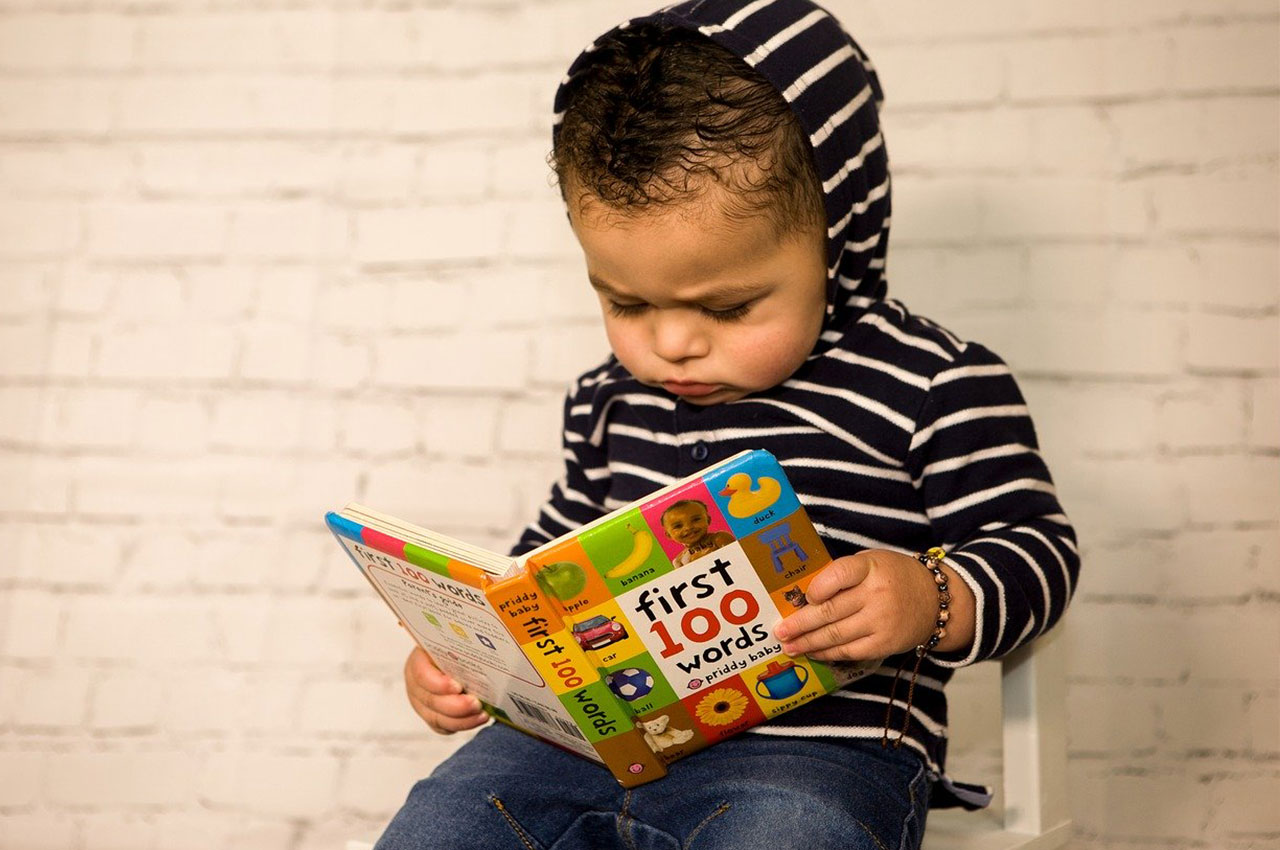 child sitting on chair reading my first 100 words children's early literacy book