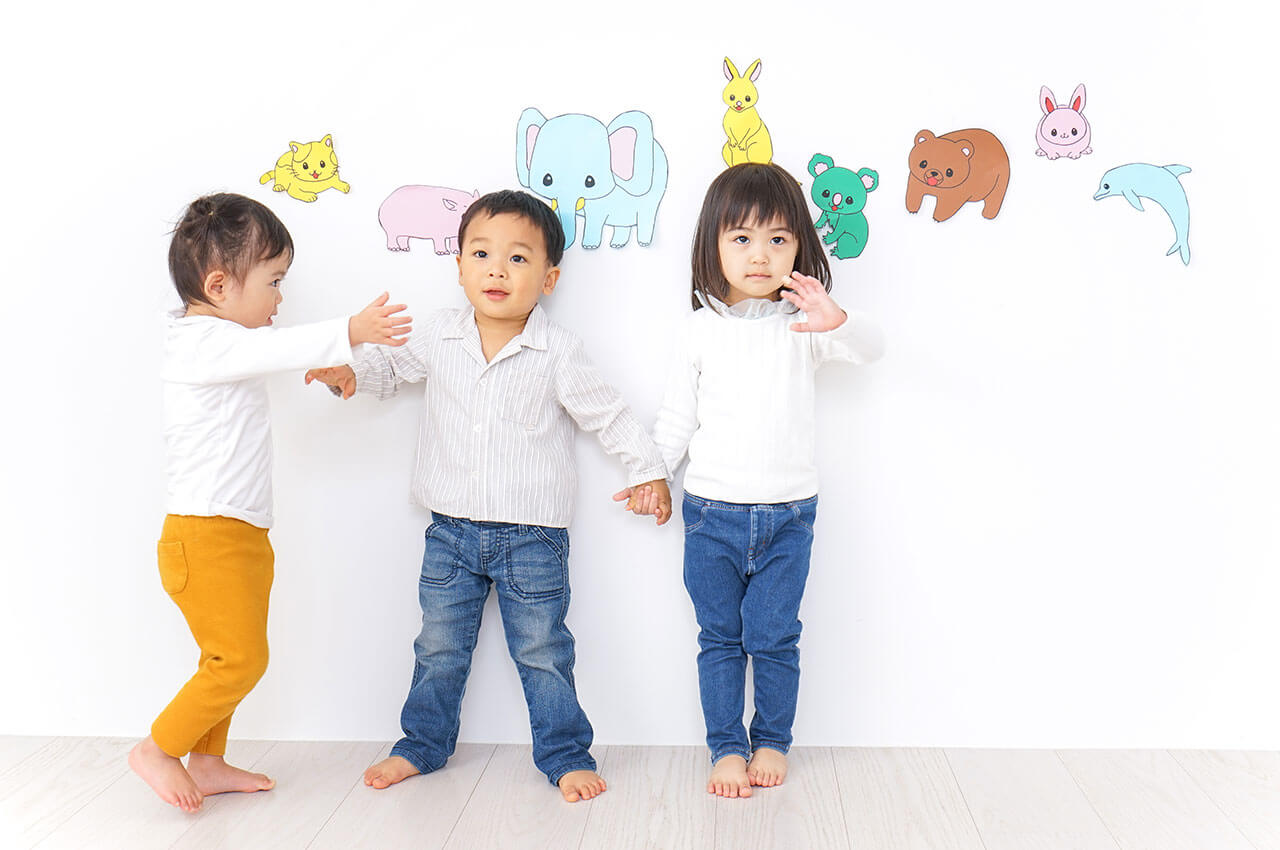3 asian toddlers standing against wall