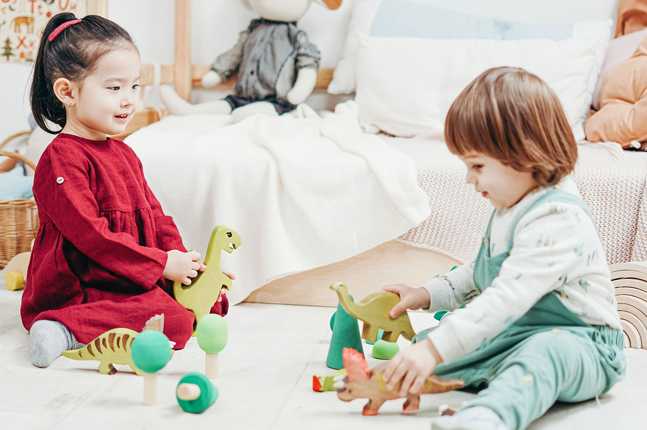two children playing with wooden dinosaur toys
