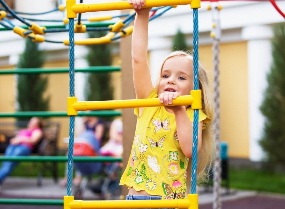 Little girl climbing rope ladder in playground