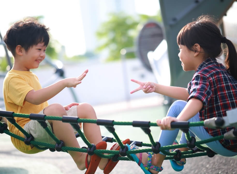 little boy and girl playing rock paper scissors on rope ladder in playground