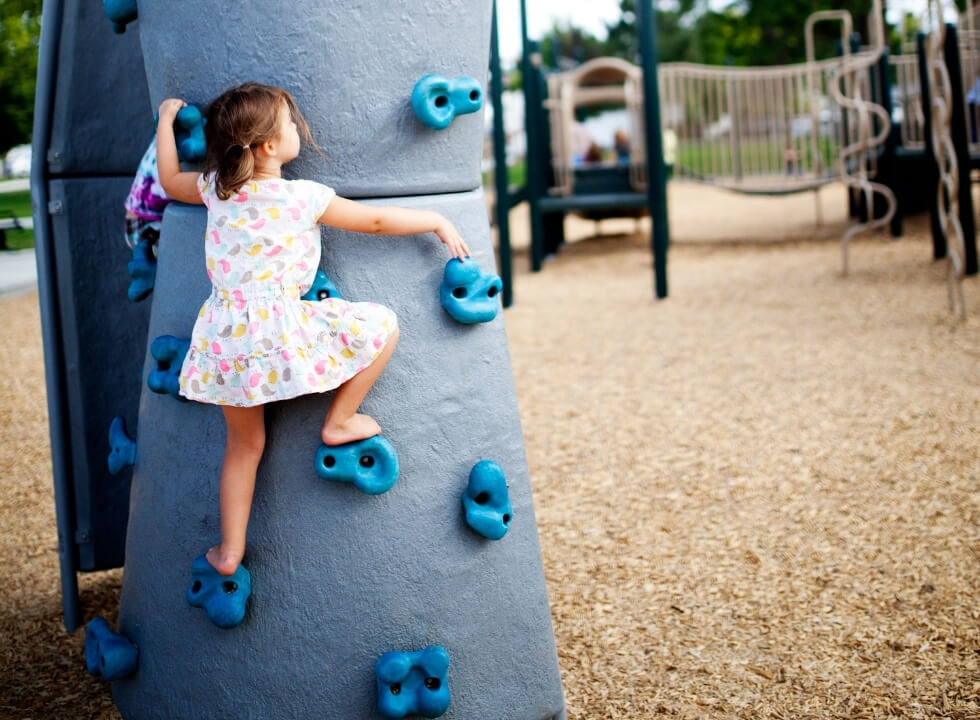 young girl rock climbing at the playground