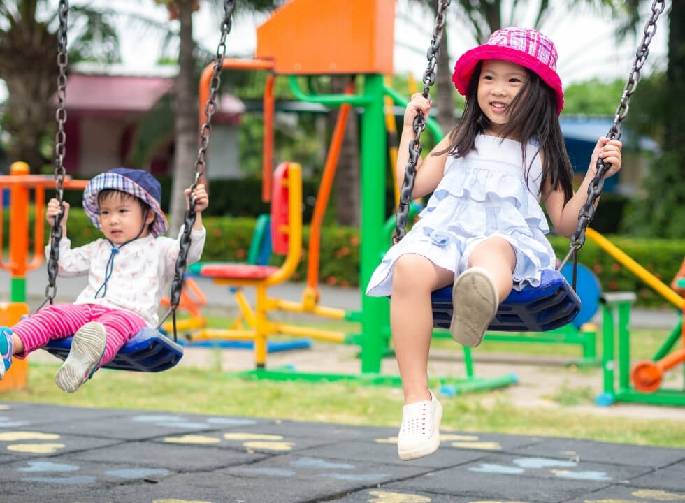 2 small children playing on swings in a playground