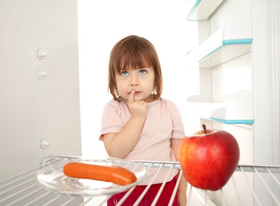 Toddler choosing between a carrot and apple